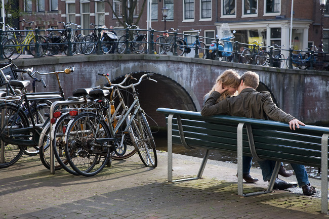 Street scene. A romantic couple by an Amsterdam Channel. The Netherlands